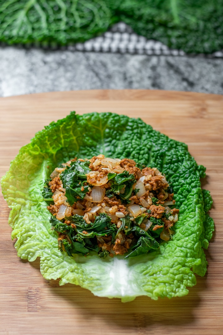 chorizo stuffing on a cabbage leaf ready to be rolled