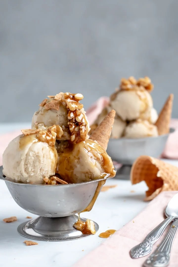 banana nice cream with wet walnuts in two silver serving bowls