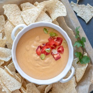 Easy Oil-Free Vegan Queso in a white bowl on a platter with chips