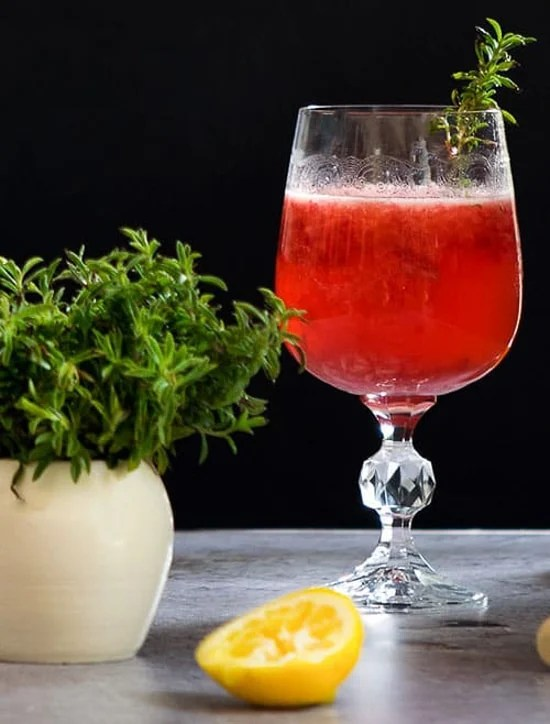 Raspberry thyme cocktail in a glass with fresh lemon and thyme