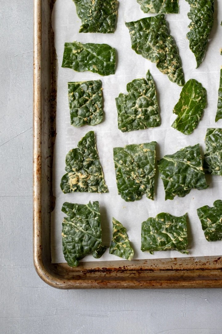 kale chips on a baking sheet ready to be go in the oven