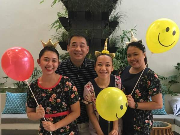 Three Front Office staff wearing unicorn head bands and holding smiley face balloons, with Dante Cruz General Manager of Ferra Hotels