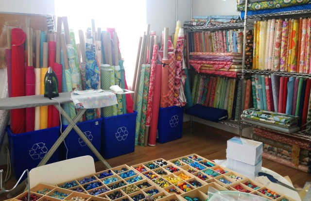 The fabric is all in one corner. I am still bringing fabric in and figuring out how best to organize it, but it's shaping up nicely. This photo was taken from Catherine's workspace, behind her bead/assembly table. The colour (of the glass and fabric together) is scrumptious.