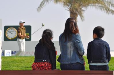 Spectators watching tee off from 18