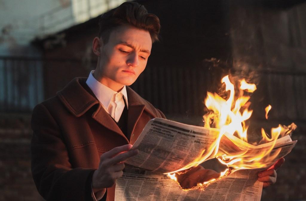 man-reading-burning-newspaper 3