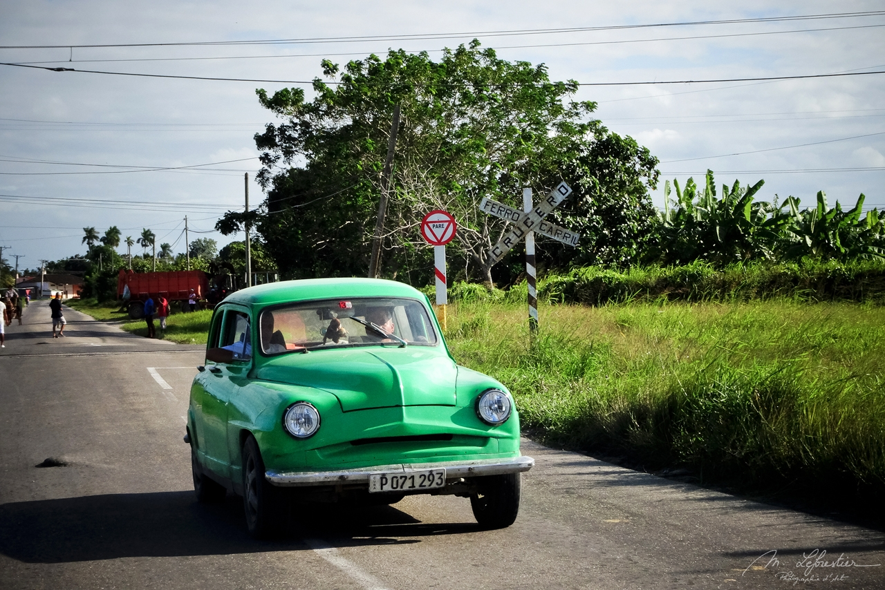 road view of an old green car from the Hershey train in Cuba