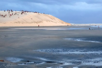 people waiting for the sunset on the dunes falling in the sea in Jericoacoara