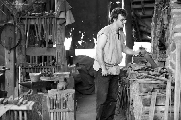 Guedelon worker in action in the build of the medieval castle in Burgundy France black and white photo