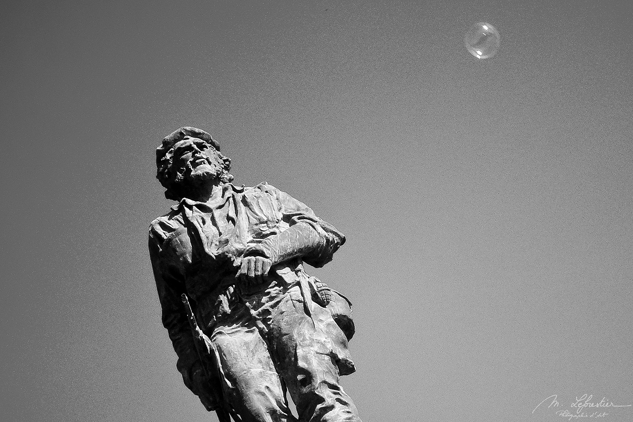 statue of the Che Guevara with a bubble in the sky in black and white