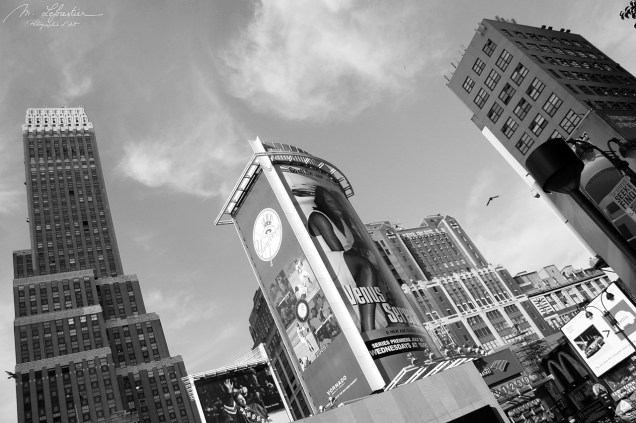 black and white photo of new york buildings and advertisements