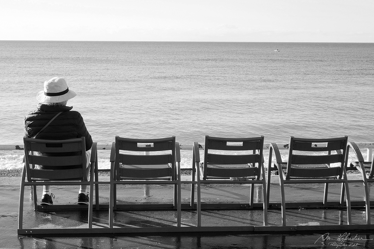 man sitting on the promenade des anglais and watching the sea