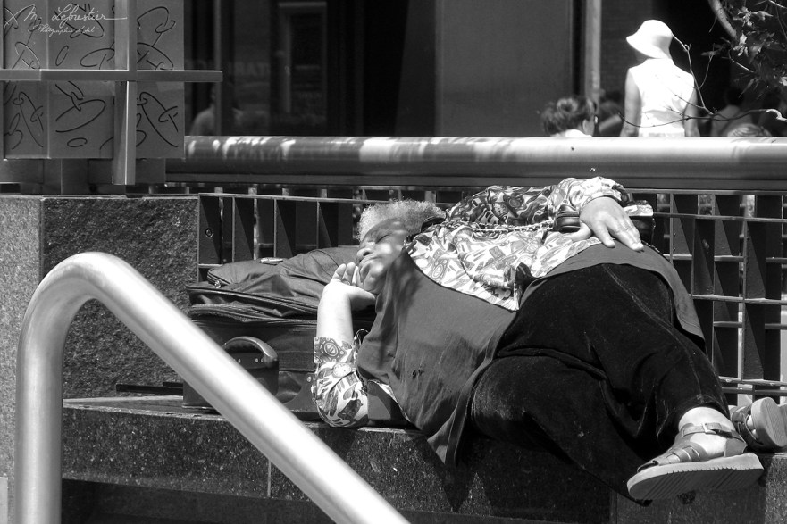 black and white capture of a woman sleeping on a bench in New York City NYC USA