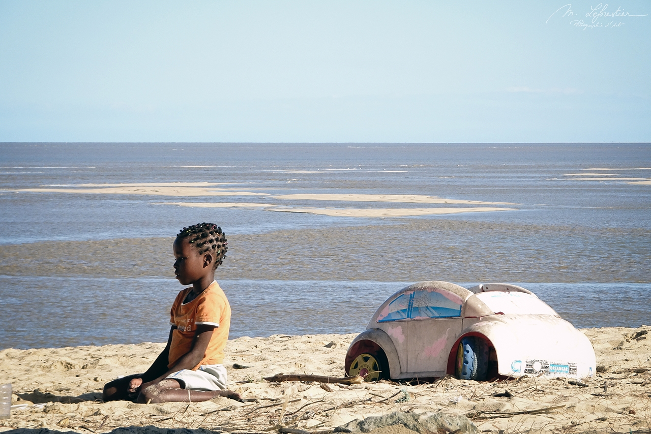 little girl playing with a miniature car in front of the indian ocean in Beira Mozambique