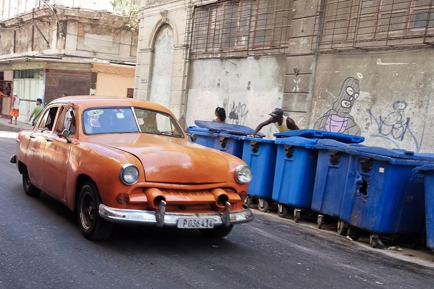 people putting trash in litter bins in a street in La Havana Cuba and an old orange car passing by