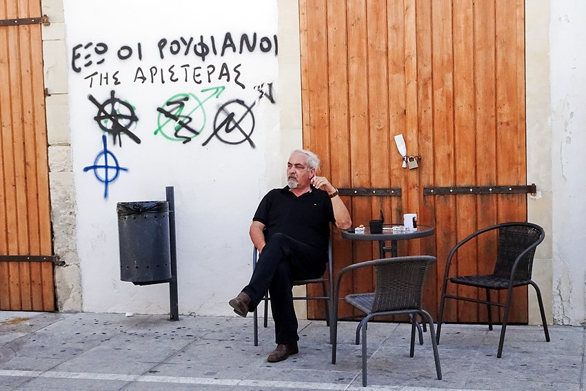 a litter bin in the street in Limassol Cyprus by a table where a man is having a cigarette