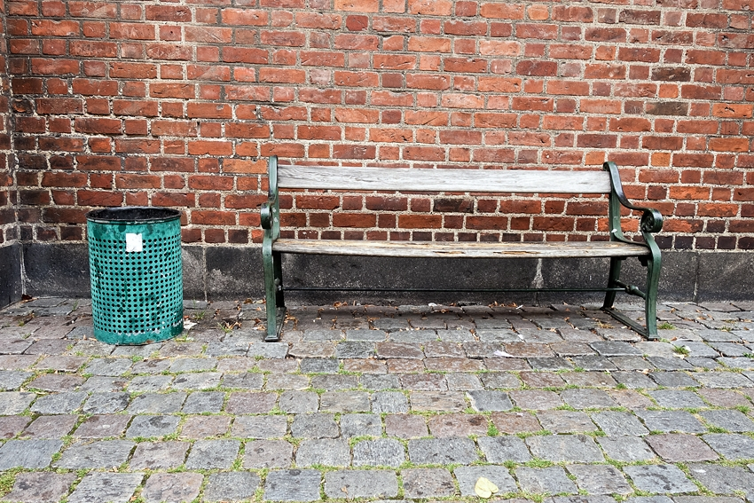a green litter bin in a street in Copenhagen Denmark by a bench