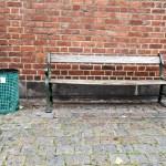 a green litter bin in a street in Copenhagen Denmark by a bench