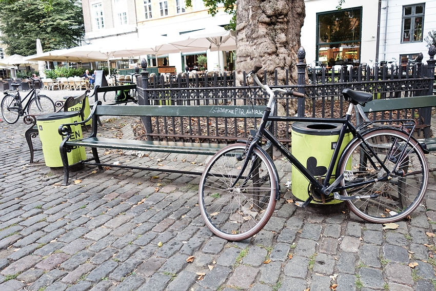 yellow litter bins in the center of Copenhagen Denmark with bicycles parked by them and some benches