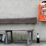 an orange litter bin hanging on a wall by a bench with a bottle on the floor that did not fit in it in Hamburg Germany