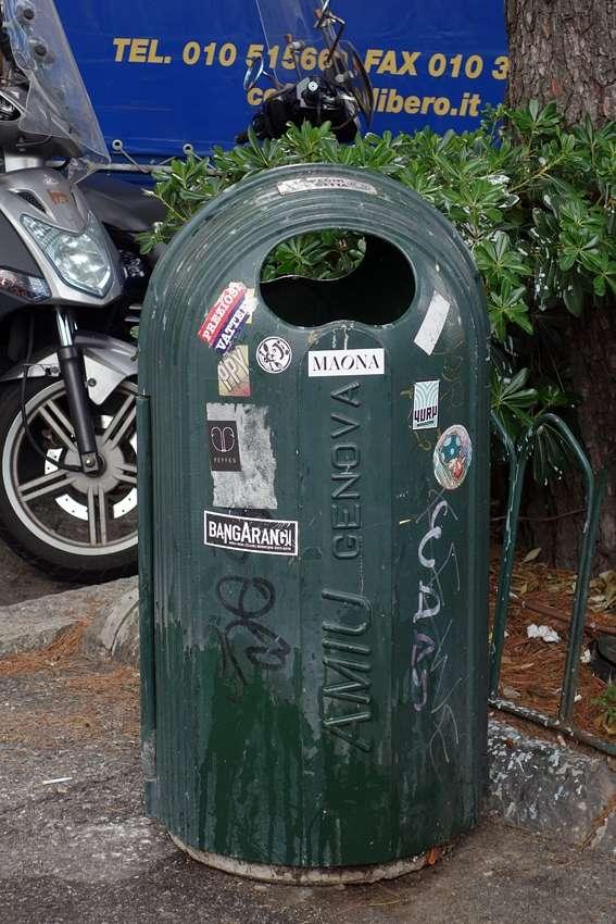 a green street litter bin full of stickers in Genova Italy