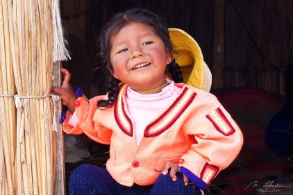 a smiling little girl with braids at Lake Titicaca in Peru