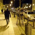 a litter bin by night in the city center of Vilnus Lithuania with people walking by in the street
