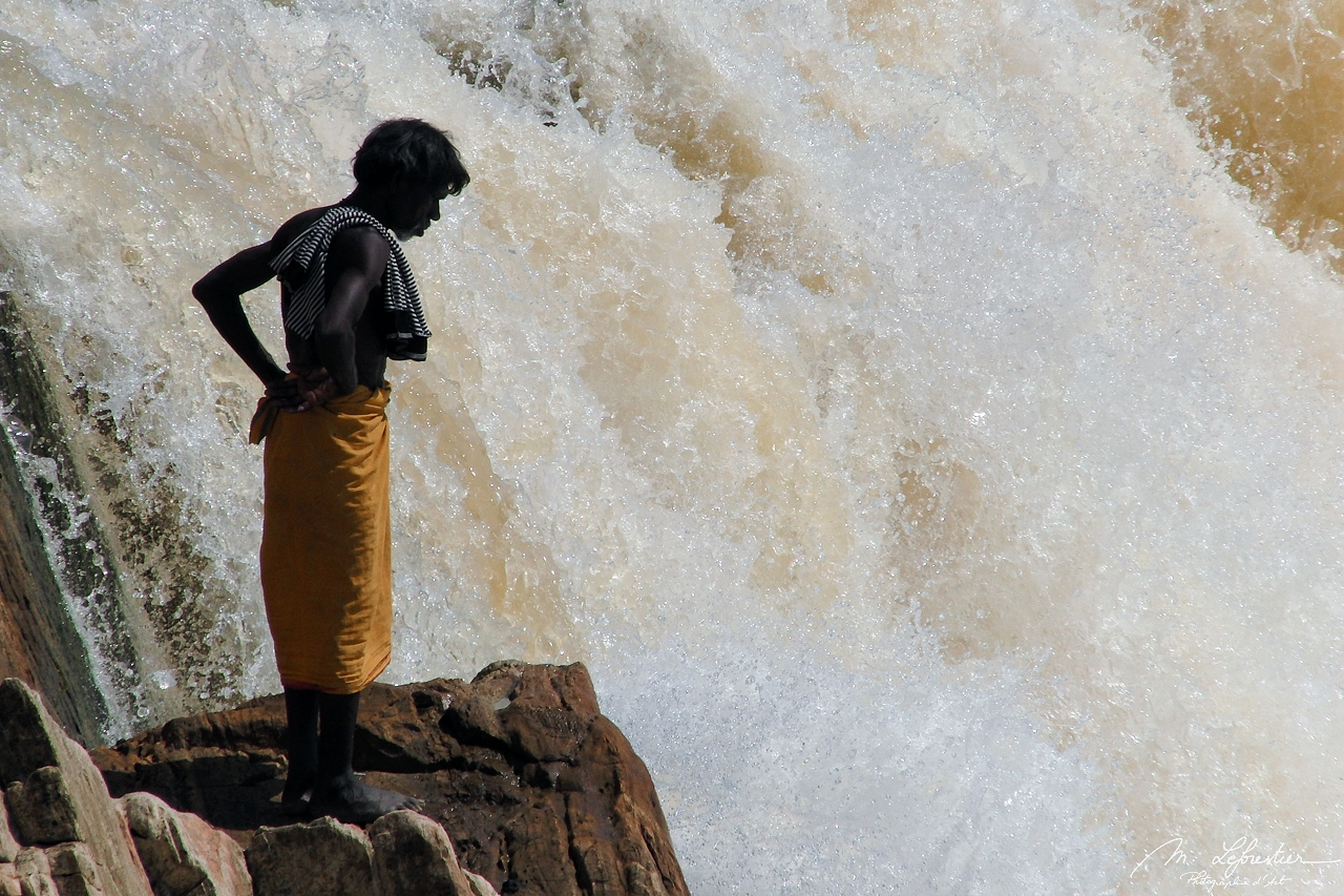 a local man is watching at the current of the Narmada river at Marble Rocks in India