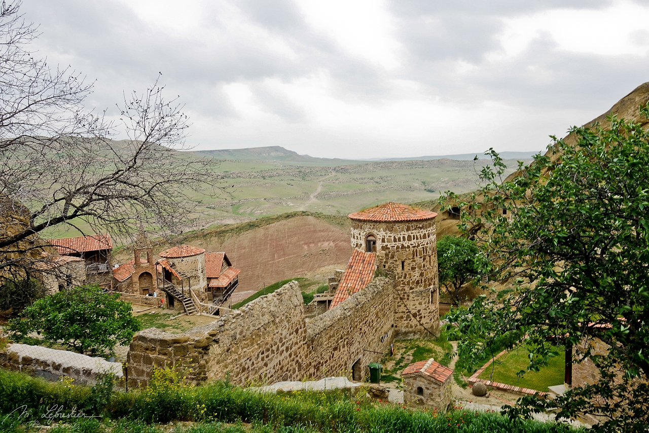 view on the stone mineral landscape in the background and in front the David Gareja orthodox monastery complex in Georgia
