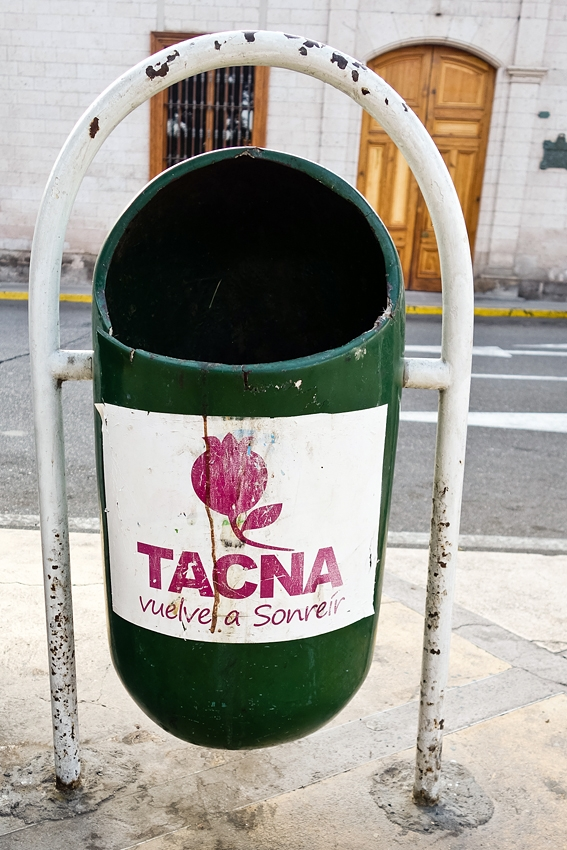 a green litter bin in a street in Tacna Peru Vuelve a soneir (start smiling again)