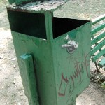 an old green trash can in a park in Bucarest Romania