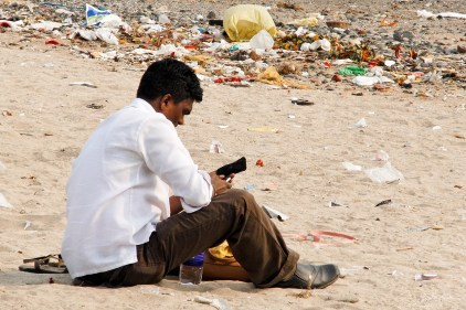man looking at his phone as he is sitting in the plastic on the Versova Mumbai beach before the clean-up
