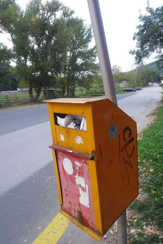 a yellow orange litter bin in a street on the way to Bratislava Slovakia