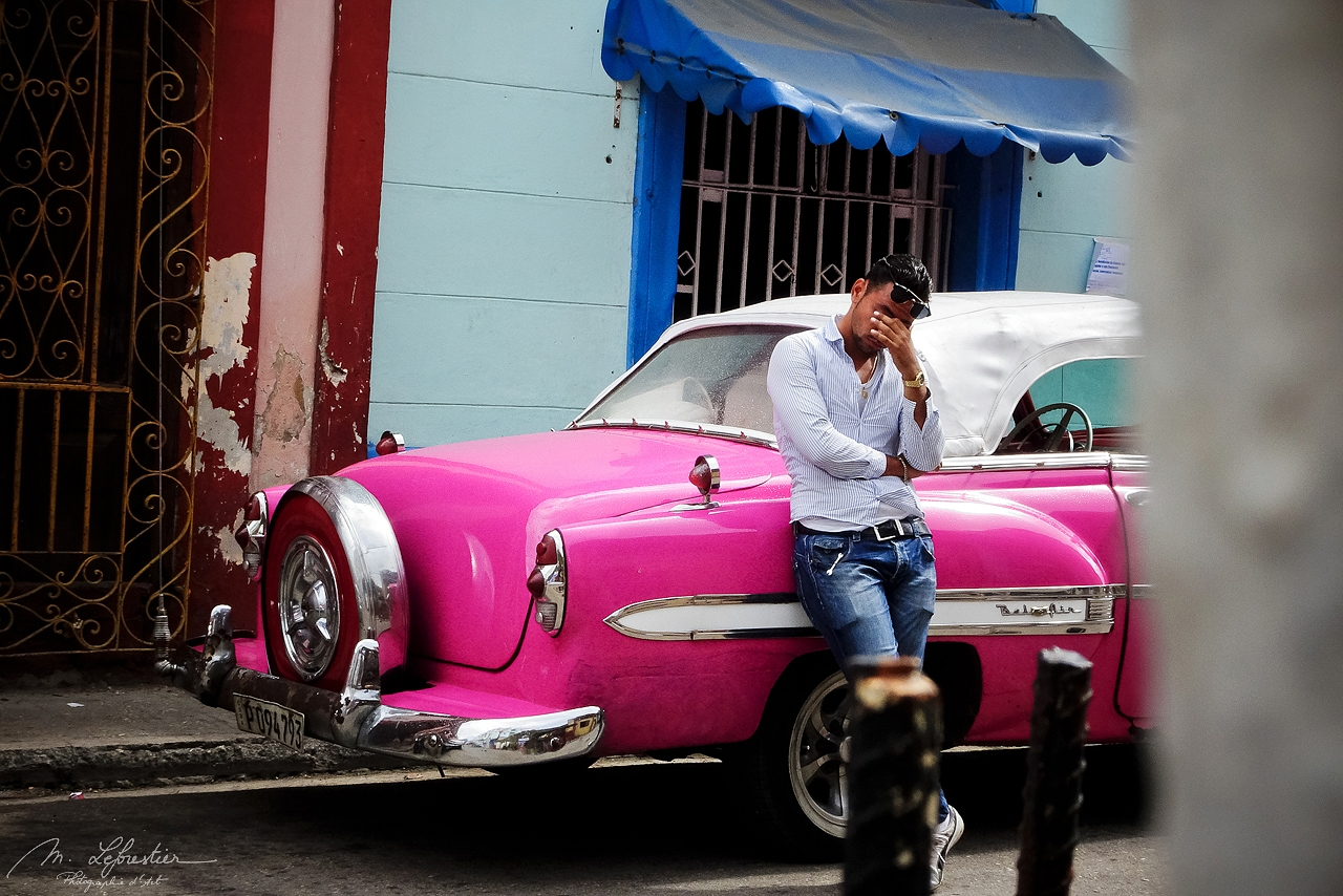 taxi driver of an old pink cuban car waiting by Callejon de Hamel for his customers in la Havana Cuba