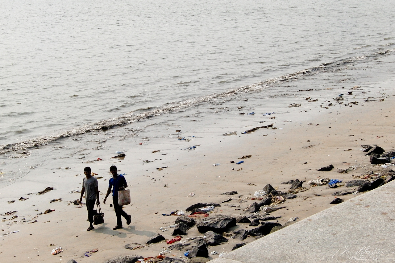 people walking in plastic on the Versova beach in Mumbai before the clean up activities