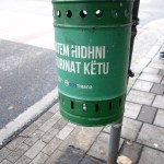a green litter bin by a stop light in Tirana, Albania