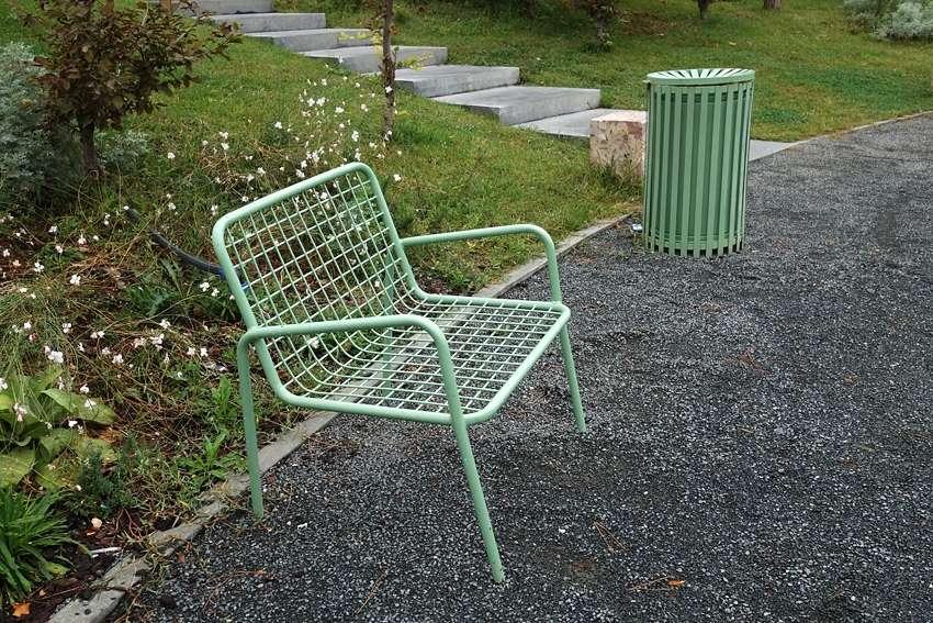 a green litter bin by a green chair in a park in Tirana Albania