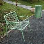 a green litter bin by a green chair in a park in Tirana Albania