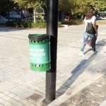 a green litter bin in a street in Tirana Albania