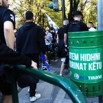 a green litter bin with locals going to the stadium in Tirana Albania to watch a football match