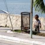 a litter boy looking at a litter bin in Flores Guatemala