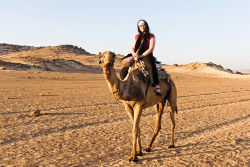 Myriam Leforestier on a camel by a nubian village in Egypt