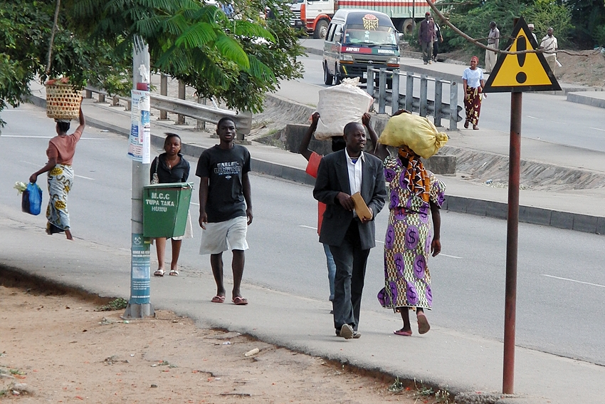 a green litter bin attached to a pole in a street of Mwanza in Tanzania