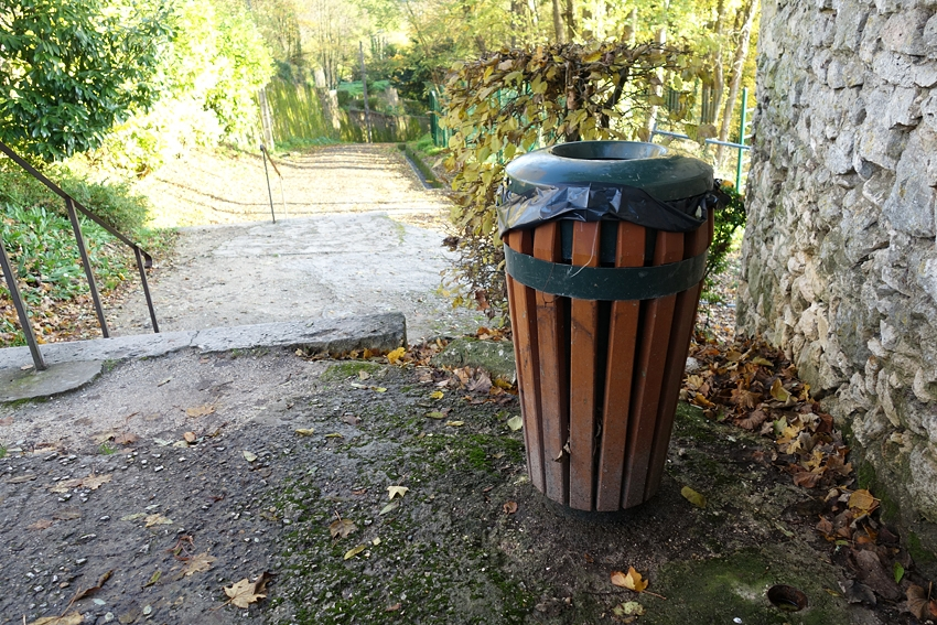 a grown litter bin with a plastic bag inside in a street of Provins France