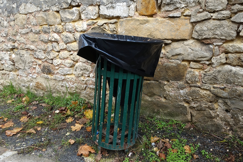 a green litter bin with a plastic bag in Provins UNESCO world site in France
