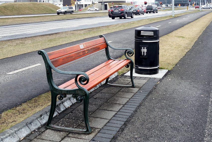 a black litter bin by a bench in Reykavik Iceland