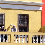 people on a balcony of a yellow house in Bo-Kaap, Cape Town , South Africa
