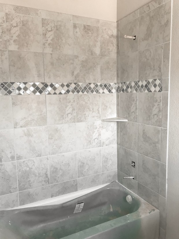 Simple gray, white, and light blue accent tile for bathroom. Adds a pop of neutral color and looks high end