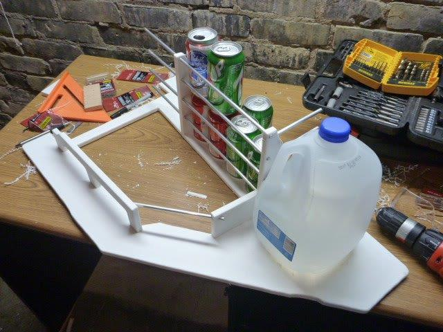 Plastic shelf with cans and a gallon water jug in place.