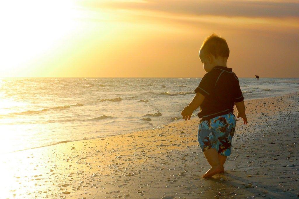 niño playa puesta de sol