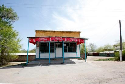 Karakol, Kirghizstan, Mai 2014. Ces guérites Coca-Cola me rappellent les cases en béton Kit-Kat que j'avais découvertes en plein milieu des rizières du sud de l'Inde il y a une dizaine d'années. En dépit du store Coca, cette boutique n'a – pas plus que les autres – grand chose à offrir. Quelques laitages, du chocolat russe, du pain élastique, des produits d'hygiène de première nécessité. Un voyageur anglais cherche des mouchoirs en papier. Je finis par me souvenir – pour avoir été enrhumée en Russie dix mois avant – qu'on appelle ça servietka. Mais c'est finalement dans une pharmacie qu'on trouvera notre bonheur.